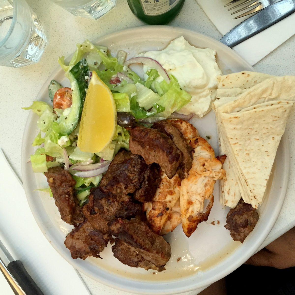 Open style souvlaki with both grilled lamb and chicken served with a Greek salad, lemon, tzatziki and pita bread