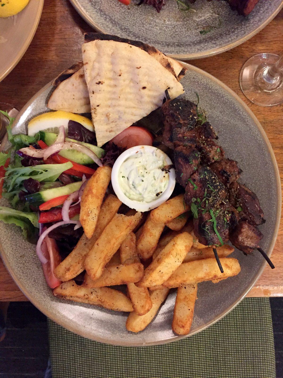 Open lamb souvlaki with tzatzki, chips, salad and pita bread